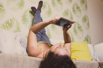 Beautiful curly woman lying on sofa and holding a tablet
