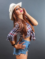 Young beautiful sexy girl in cowboy hat on grey background.