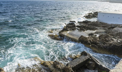 Tourism cliff next to the Mediterranean Sea, strong waves break with the rocks and leave blue and turquoise colors along with the foam of the sea.