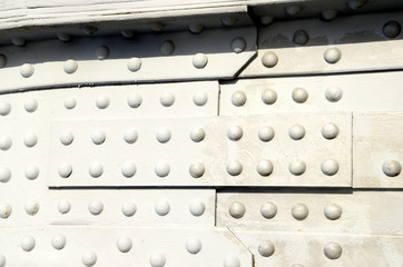 Closeup on elder gray steel structure with a lot of rivets.