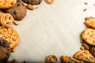 on the baking paper on the edges of the frame with a place under the text in the center lie round oatmeal cookies with chocolate and nuts, next to peanuts and almonds