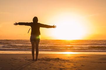 Woman looking at the horizon, beach at sunset