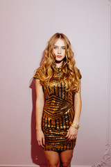 fashion portrait of a beautiful girl in gold luxury dress on the pink background. vertical photo