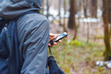Man hand holding smart phone device in the forest and looks at the map