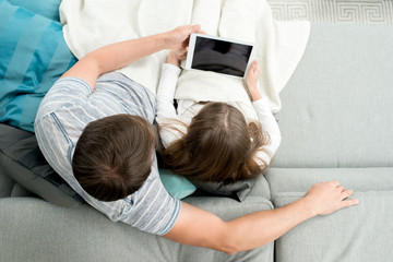 Above view of father using digital tablet enjoying evening with teenage daughter and watching movies, copy space