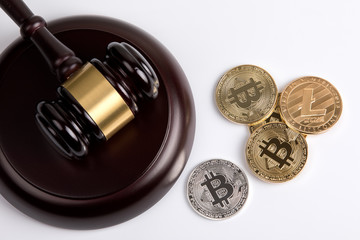 crypto currency. Golden Bitcoin, Litecoin with a wooden judges gavel on white background.