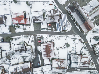 Aerial view of rooftops of German town in winter. Everything covered with snow