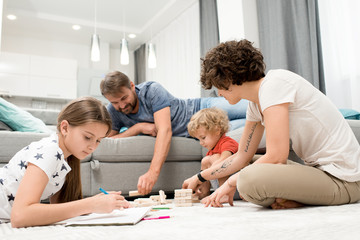 Portrait of happy young family of four enjoying evening together drawing with children on floor in living room