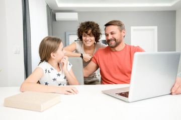 Portrait of happy family of three using laptop sitting together at home in living room