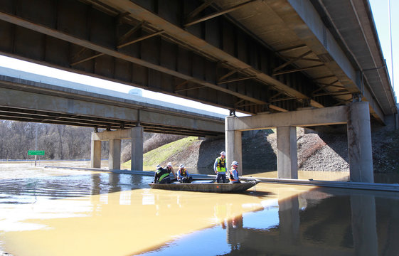 Employees of Louisville Gas & Electric make their way under Interstate 71 to River Road to turn off power to companies along the Ohio River after it flooded Louisville