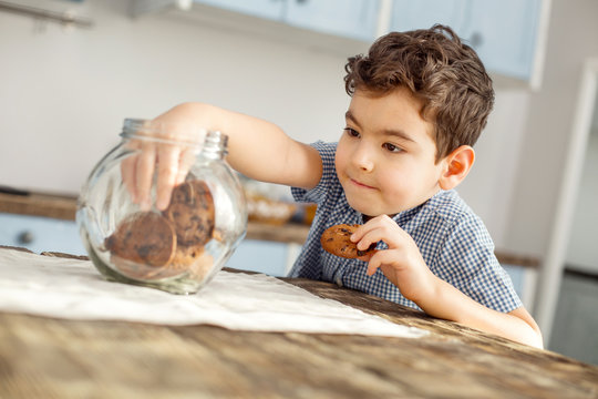 I love cookies. Handsome delighted little dark-haired boy sitting at the table and eating a cookie and taking some more