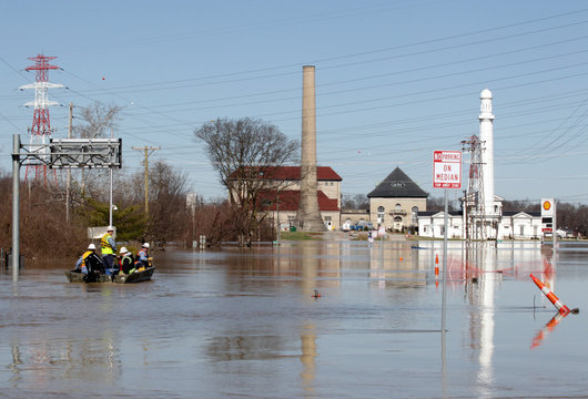 Employees of Louisville Gas & Electric make their way to River Road to turn off power to companies along the Ohio River after it flooded Louisville