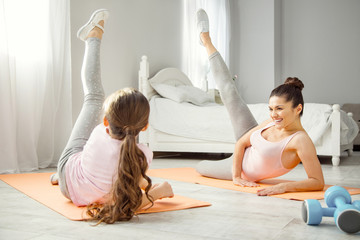 Favourite activity. Beautiful inspired young dark-haired mother doing some exercises for legs with her daughter while lying on the floor and looking at her girl