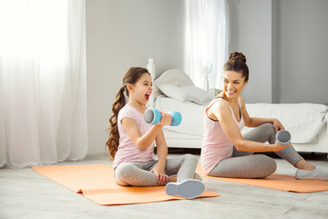 Our hobby. Beautiful delighted young dark-haired mother doing some exercises with hand weights with her daughter while sitting on the floor and looking at her girl