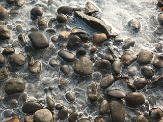 Close up of frozen water with stones in the river