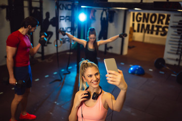 Young sporty woman taking a selfie with mobile phone for social networks at gym. In background her friends doing exercises.