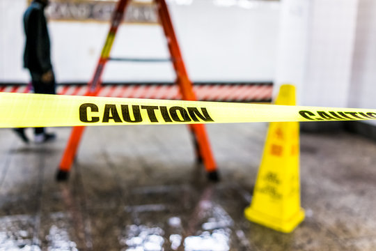 Caution tape sign in underground transit empty large platform in New York City NYC Subway Station in Grand Central, ladder, wet floor cone