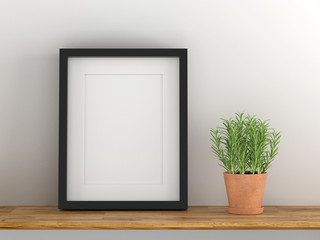 Blank black picture frame template for place image or text inside with a little tree on wood table.
