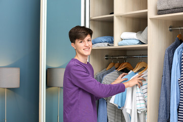 Teenager choosing clothes in wardrobe at home