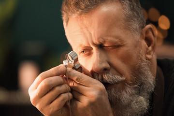 Jeweler evaluating gem with magnifier at workshop