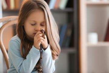 Religious Christian girl praying indoors