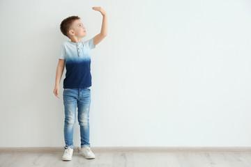 Little boy measuring height near light wall