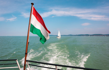 Lake Balaton from a ship deck with a hungarian flag in Hungary.