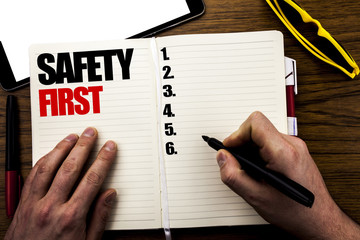 Word, writing Safety First. Business concept for Safe Warning Written on book, wooden background with businessman hand, finger writing on the notebook.