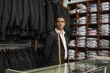 Tailor looking away while standing at store