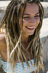 Close-up of cheerful young woman with dreadlocks