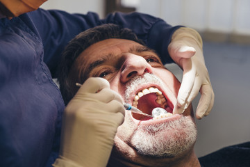 Close up of dentist using mouth mirror while examining patient's teeth