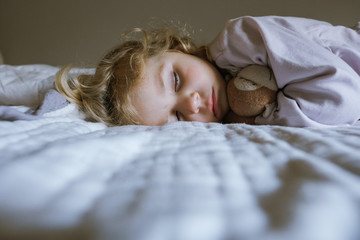 Cute girl with toy sleeping on bed at home
