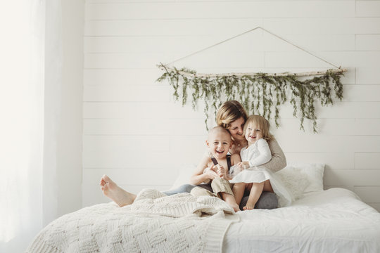 Happy mother with children sitting on bed at home