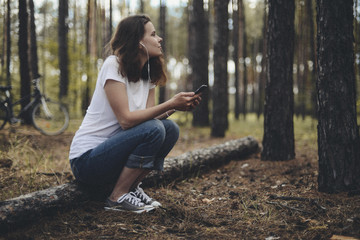 Side view of woman listening music while sitting on field in forest