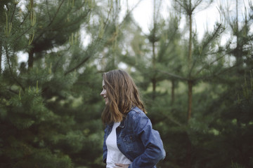 Side view of woman looking away while standing in forest