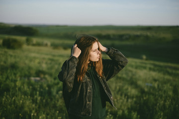 Woman looking away while standing on green landscape against sky during sunset