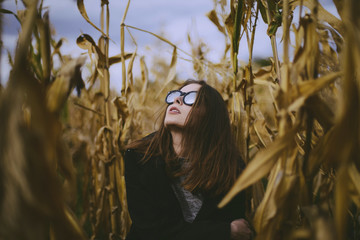 Woman wearing sunglasses sitting amidst crops at farm against sky