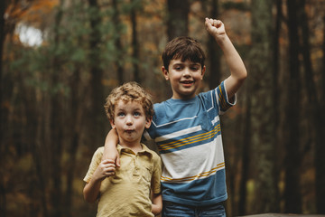 Portrait of boy with brother standing at park