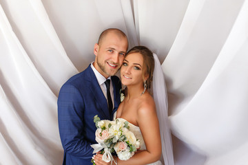 Wedding portrait of happy marriage couple, newlyweds in love, bride and groom smiling and looking to camera on white background