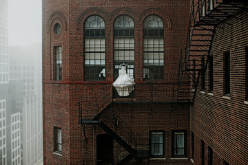 Wedding gown hanging by fire escape of building in city Wall mural