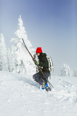 Side view of hiker with backpack and ski walking on snowy hill during winter