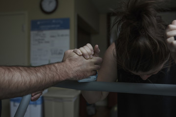 Cropped hand of man comforting painful pregnant woman in hospital ward