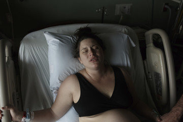 Painful pregnant woman lying on hospital bed