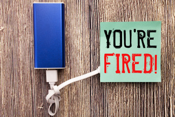 Handwritten text caption showing You Are Fired. Business concept writing for Unemployed or Discharge written on sticky note with copy space old wood wooden background with power bank