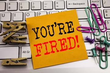 Writing text showing You Are Fired. Business concept for Unemployed or Discharge written on sticky note paper on the white keyboard background.