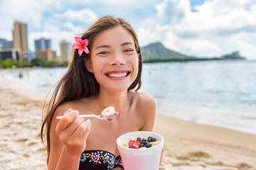 Acai breakfast smoothie bowl eating woman enjoying hawaii food on Waikiki beach, Honolulu. Asian girl happy smiling on detox diet eating healthy local fruit snack.