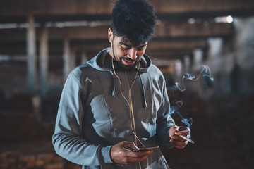 Portrait of hipster afro-american young handsome man relaxing outside on the street at night with earphones and cigarette while choosing music on a mobile.