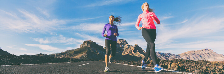 Running active people training outside banner panoramic landscape. Two women jogging together exercising cardio in summer outdoors nature.