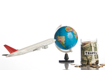 Holidays budget concept. Travel money savings in a glass jar with flying plane toy and world globe map on a white background, close-up