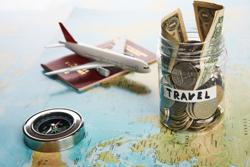 Holidays money savings in a glass jar with compass, passport travel document and plane toy on world map, close-up. Travel budget concept.